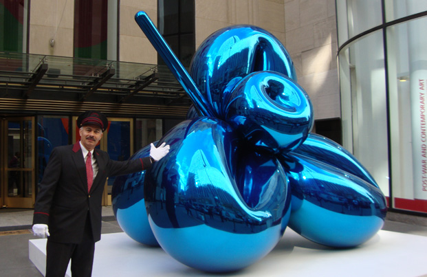 "Gil Perez of Christie's with ""Balloon Flower (Blue)"" by Koons"