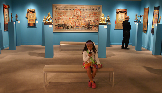 Young girl with Ipod taking a break from Indian Art