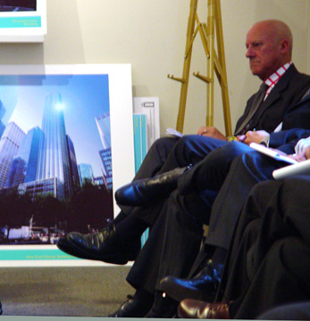Sir Norman Foster sitting beside rendering of tower