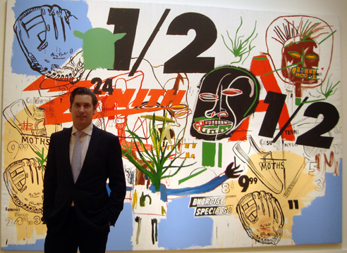 "Alex Rotter of Christie's standing in front of ""Untitled"" by Warhol and Basquiat"